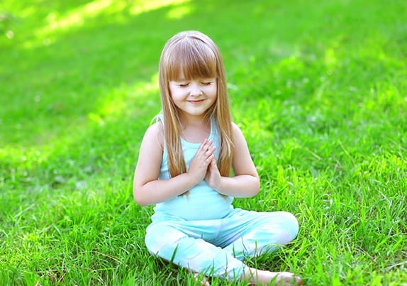 Child doing yoga exercises sitting on the grass in sunny summer day