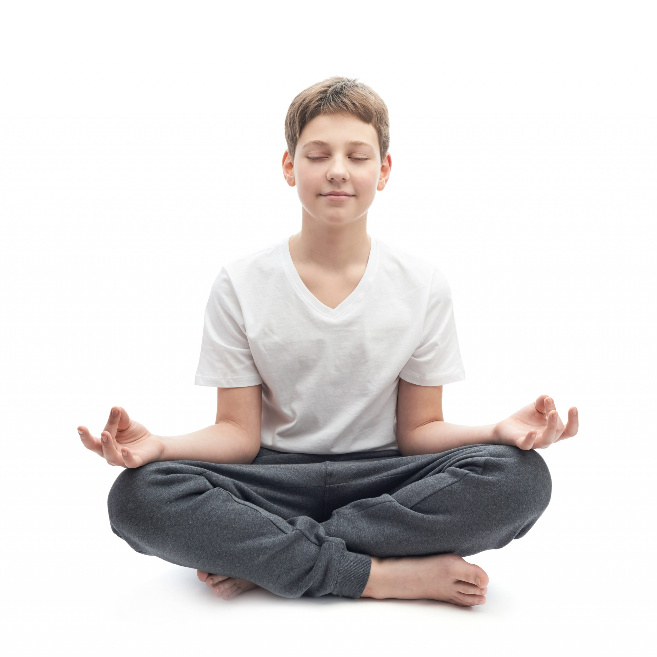 Meditating caucasian 12 years old children boy in a white t-shirt, composition isolated over the white background